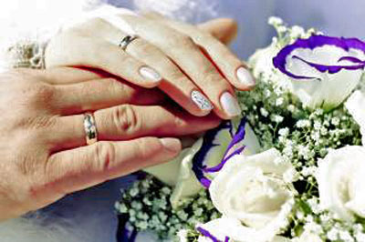 An image of hands with wedding rings.