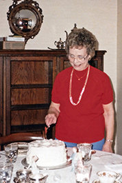 A photographic image of Mom Webb cutting a cake on her 66th birthday.