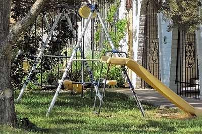 A photographic image of a swing set near a tree.