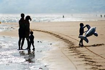 A photographic image of a family at a beach.