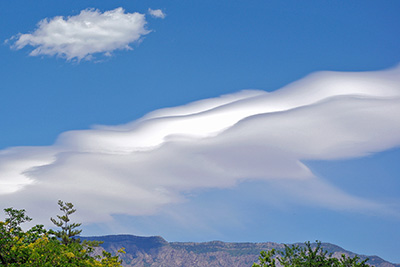 A photographic image of virga flowing out of a mountain wave cloud.