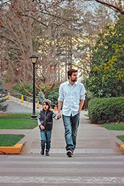 A photographic image of a father walking with his son.