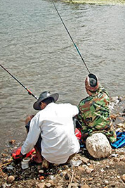 A photographic image of two men fishing.