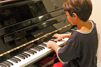 A photographic image of a boy playing a piano.