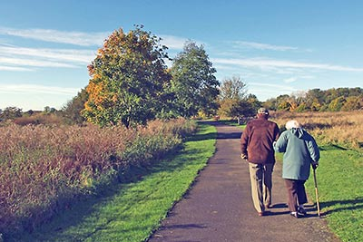 A photographic image of an elderly couple walking on a country path.